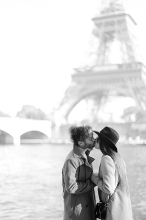 Afro american man kissing woman in hat near Eiffel Tower, Paris. Concept of love and France tour.