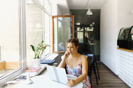 Young female thoughtful student sitting at cafe with laptop and surfing internet. Concept of modern technology. Stock Photo