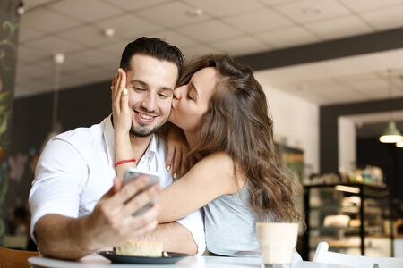 Young wife kissing husband using smartphone at cafe and eating cake. Concept of food and drink, happy couple and relationship, modern technology. Reklamní fotografie - 133182393