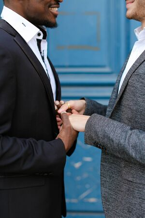 Afro american smiling man holding hands of caucasian guy in door background, wearing suit. Concept of same sex couple and gays.