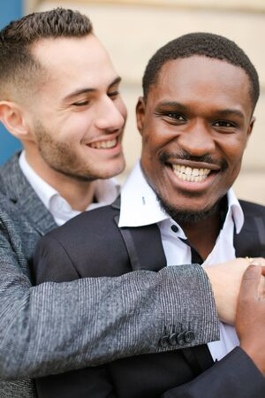 Portrait of two hugging smiling boys, caucasian and afro american, wearing suits. Concept of gays and lgbt.