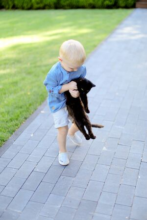 Little blond playing with black cat outdoors. Concept of childhood and pets.