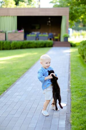 Little boy in jeans shirt standing with cat in yard. Concept of kids, childhood and pets.