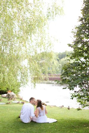 Young couple sittling near lake on grass and kissing. Concept of relationships, youth and love.