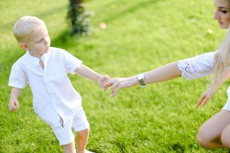 Young mother holding child hand in green grass background. Concept of motherhood and kid.