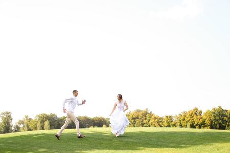 Groom and pretty bride running and playing on grass. Concept of wedding photo session on open air and nature. Banque d'images