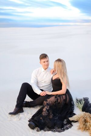 Young girl wearing black dress and man sitting on snow in steppe. Concept of winter photo session and love.