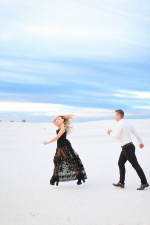 Young female person and man running on snow, wearing black transparent dress. Concept of winter photo session and happy couple. Banco de Imagens