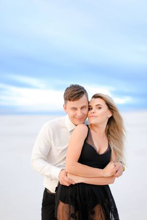 Young man hugging woman in white snowing background in steppe. Concept of winter photi session and romantic love.