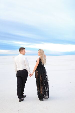 Back view of young girl in black transparent dress holding man hands and walking in winter steppe. Concept of seasonal photo session and love.