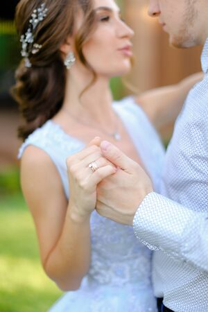 Close up fiancee dancing with groom outside, focus on hand rings. Concept of wedding and bridal photo session.