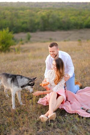 Young happy woman and man sitting on pink plaid near husky and resting outside. Concept of picnic on nature and dogs.