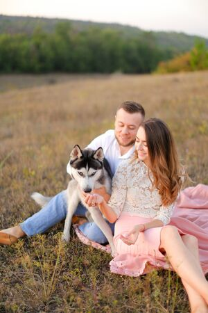 Young woman and man sitting on gras with malamute. Concept of relatonship, picnic and dog. Banco de Imagens