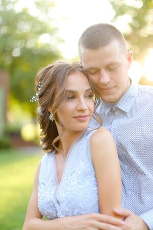 Happy handsome groom hugging fiancee in park, sun rays. Concept of bridal couple and wedding photo session in open air.