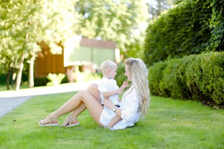Young euopean mother sitting with little child on grass in yard. Concept of motherhood and summer vacations.