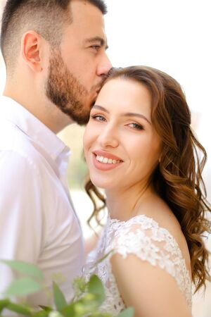 Happy caucasian groom kissing bride keeping bouquet of flowers. Concept of love and wedding photo session. Reklamní fotografie - 133182707
