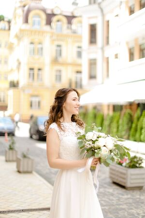 Caucasian charming fiancee walking with bouquet of flowers in city. Concept of bridal photo session.