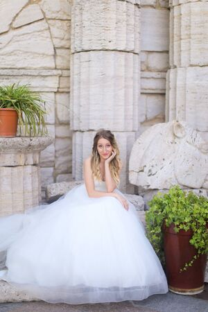 Caucasian pretty fiancee sitting near ancient columns and wearing white dress. Concept of bridal photo session and wedding.