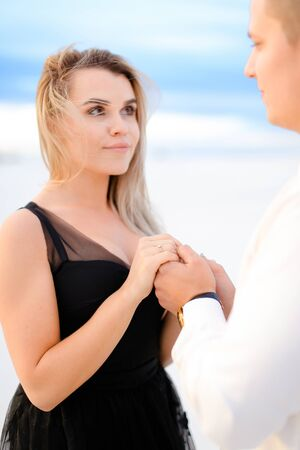 Young girl holding man hands in white background. Concept of love nad winter photo session.