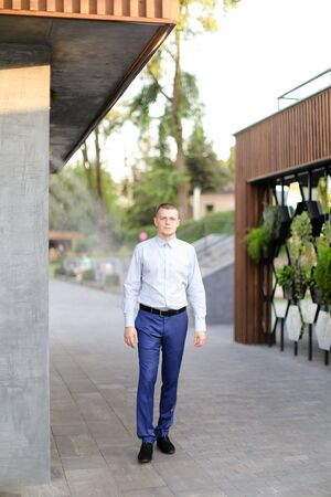 Caucasian young european man standing outside and wearing shirt. Concept of male person.