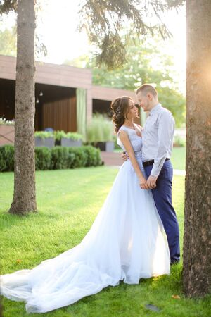 Caucasian young fiancee dancing with groom in park and wearng white dress. Concept of married couple and bridal photo session in open air.