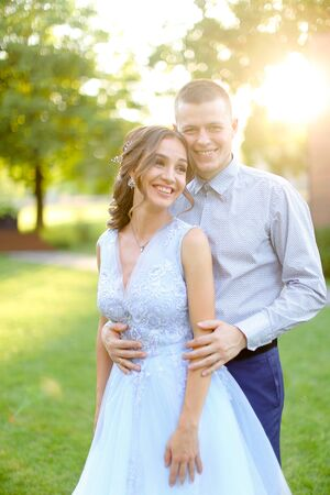 Happy smiling groom hugging fiancee in park, sun rays. Concept of bridal couple and wedding photo session in open air.