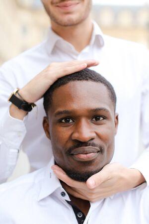 Caucasian man holding afro american guy head by hands. Banco de Imagens