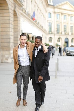 Caucasian smiling man in suit walking with afroamerican male person and hugging in city. Concept of happy gays and strolling. Banco de Imagens