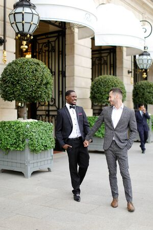 Afro american and caucasian happy gays walking outside and holding hands in city. Concept of same sex male couple.