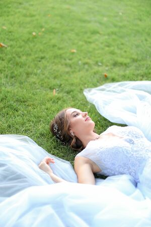 Innocent fiancee lying on grass in oark and wearing white dress. Concept of beauty and bridal photo session in open air.