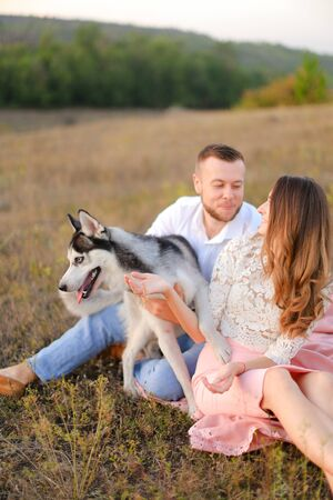 Young caucasian woman and man sitting on gras with malamute. Concept of relatonship, picnic and dog. Banco de Imagens
