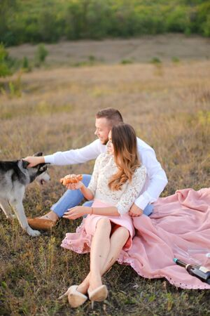 Young happy girl and man sitting on grass plaid and playing with husky. Concept of picnic on nature and dogs.
