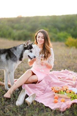 Young nice girl sitting on pink plaid in steppe near dog malamute. Concept of picnic on nature and pets.