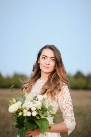 Caucasian beautiful fiancee with white bouquet background in steppe background. Concept of bridal photo session on nature and floristic art.