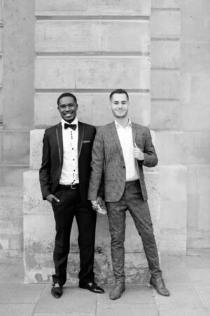 Black and white photo afro american and caucasian happy gays standing near building and wearing suits. Concept of lgbt and walking in city. Banco de Imagens