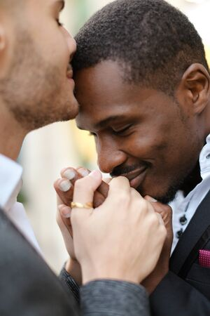 Caucasian man kissing afro american man forehead and holding hands. Concept of lgbt and same sex couple.