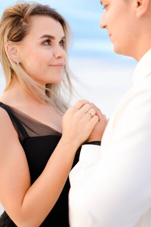 Young blonde woman holding man hands in white background. Concept of love nad winter photo session. Banco de Imagens