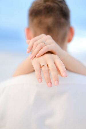 Back view of female arms holding man neck. Concep of love.