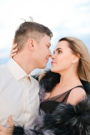 Portrait of man hugging woman wearing fur coat in white background. Concept of love nad relationship. Banco de Imagens