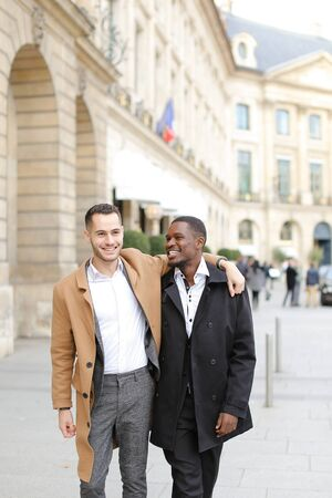 Caucasian happy man in suit walking with afroamerican male person and hugging in city. Concept of gays and strolling.