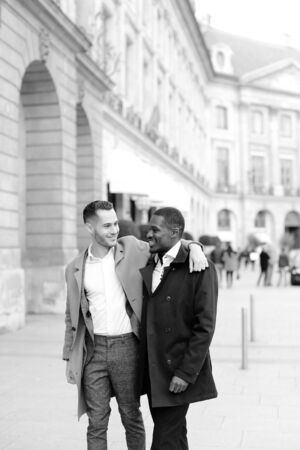 Caucasian man in suit walking with afroamerican male person and hugging in city. Concept of happy gays and strolling. Banco de Imagens
