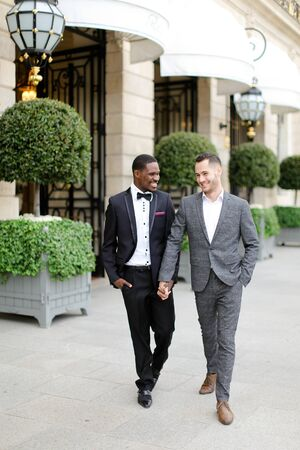 Afro american and caucasian happy handsome gays walking outside in city. Concept of same sex male couple. Banco de Imagens
