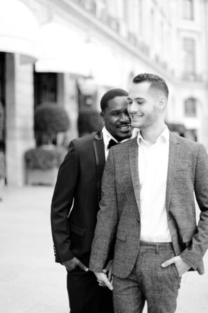 Black and white photo of afro american handsome man hugging european boy wearing suit. Concept of gays and same sex couple.