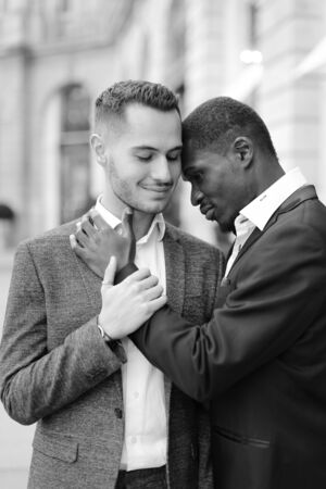 Black and white photo of afro american gay hugging caucasian boy outside, wearing suits. Concept of lgbt and same sex couple. Banco de Imagens