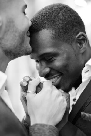 Balck and white photo of caucasian man kissing afro american boy forehead and holding hands. Concept of lgbt and same sex couple.