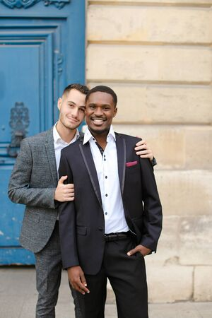 Two boys, caucasian and afro american, wearing suits standing near building and hugging. Concept of gays and lgbt. Banco de Imagens