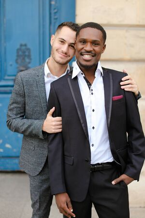 Two smiling boys, caucasian and afro american, wearing suits standing near building and hugging. Concept of gays and lgbt.