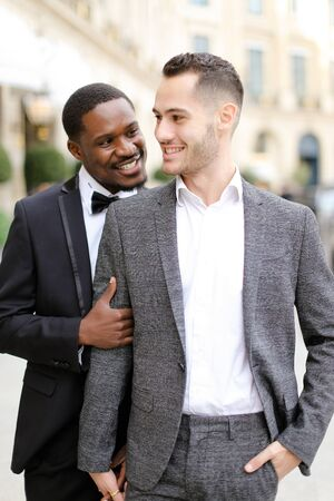 Afro american man hugging european boy wearing suit. Concept of gays and same sex couple.