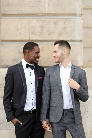 Afro american and caucasian smiling gays standing near building and wearing suits. Concept of lgbt and walking in city. Banco de Imagens