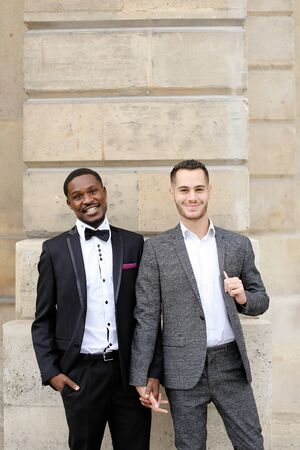 Afro american and caucasian happy smiling gays standing near building and wearing suits. Concept of lgbt and walking in city. Banco de Imagens